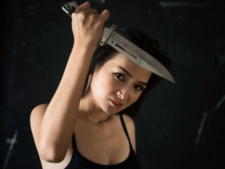 Psychosis sadism woman murderer hold knife and look at camera with dark black background and copy space for text. Crime, Drug, Abuse, Mental sickness for safety concept. 免版税图像