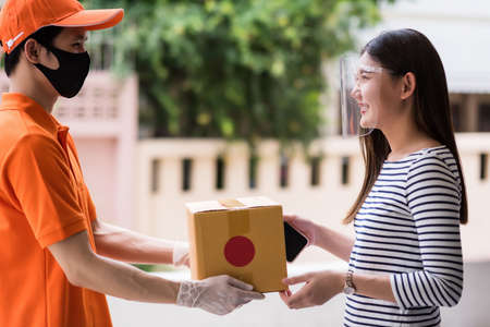 Asian beautiful woman with face shield accept delivered online packaging in cardboard boxes from deliveryman with face mask and glove in orange uniform. COVID-19 pandemic outbreak. New normal 免版税图像