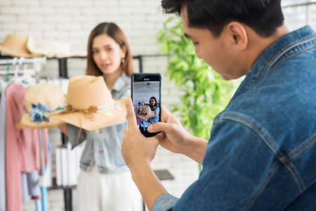 Record video streaming online by smartphone of beauty blogger or Stylist popular influencer girl selling fashion hat. Opinion leader trend on her online blog channel. New normal of e-commerce.