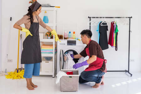 Bossy housewife demand her husband or boyfriend to laundry dirty clothing in washing machine by himself. Housework chore to man while lazy wife control his work.