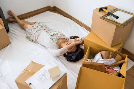Young tired Asian woman moving in new home, sleep or nap during unpack stuff near cardboard box, blueprint plan paper and suitcase. Start new life. House mortgage loan and refinance concept.