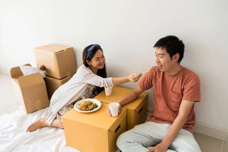 Young Asian couple sit on floor and eat roasted duck egg noodle on cardboard moving boxes to be unpacked stuff at new house. Home mortgage loan and Real estate to start new family life. 免版税图像