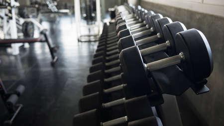 metal dumbbells on rack shelf for physical bodybuilding strength training in fitness gym