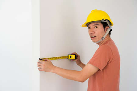 Asian Interior engineer man with yellow hardhat using measuring tape to measure empty wall of new house. Furniture or cabinet built in for modern blank home. Real estate industry.