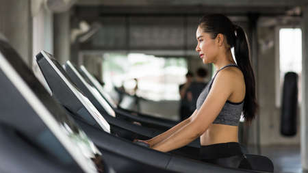 Asian attractive sporty woman walk cardio training on treadmills to warm up before running in fitness gym with copy space for text. Bodybuilding and healthy lifestyle concept.