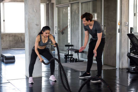 Athlete Asian woman doing battle rope exercise with motivating by American sport personal trainer in fitness gym. workout, coaching, bodybuilding healthy lifestyle concept.