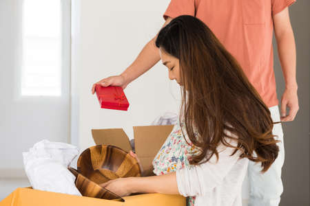 Man giving surprise gift to Asian woman during unpacked stuff on cardboard boxes. surprised present to wife of first day moving to new house. Start new couple life.