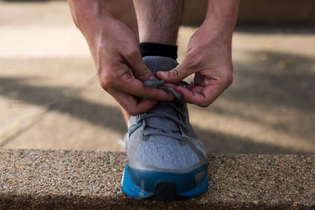 Man athlete Runner hands tying running shoes or shoelace on footpath with sunset light before running. Bodybuilding and Healthy lifestyle concept.