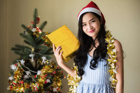 Smile beauty Asian Woman with Santa Claus hat hold gold Xmas gift box from boyfriend near Christmas tree. Happy girl celebrate 2021 New Year and Christmas.
