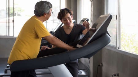Asian senior 60s aged man cardio exercise on treadmill with Personal trainer workout in fitness gym. Bodybuilding and Healthcare sport trainnig for retired old guy or elderly.