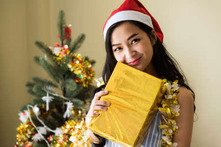 Smile Attractive Asian Woman with Santa Claus hat hold gold Xmas gift box from boyfriend near Christmas tree. Happy girl celebrate 2021 New Year and Christmas. 免版税图像