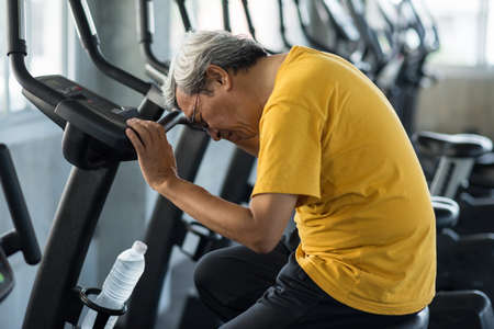 Exhausted blackouts senior 60s man after biking exercise in fitness gym. Old guy with gray hair head down due to shock, heart attack, dizzy. Elderly accident from sport training. Healthy and insurance