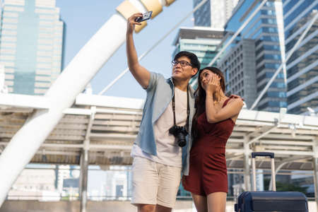 Asian Korean tourist couple taking selfie photo from smartphone with travel suitcase and dslr camera in modern urban city at summer. Happy travel vacation for young man and woman. 免版税图像
