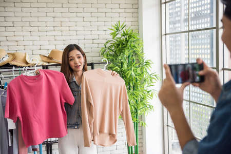 live video streaming by smartphone to sell woman shirt by female fashion blogger or Stylist popular influencer girl in studio. Opinion leader trend on her online blog channel. New normal of seller.