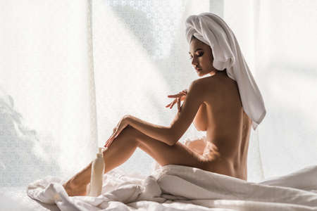Beautiful young Asian woman wrapped in shower towel sit on bed and apply moisturising cream lotion for body treatment on bed. Sexy nude tan girl perform skin care. 免版税图像
