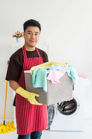 Asian handsome man wearing red apron and yellow rubber gloves smiling while carrying laundry basket with clothes near washing machine. Housework during weekend.