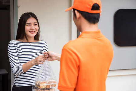 Attractive beautiful Asian woman take bakery food in plastic bag from deliveryman in uniform. Office businesswoman order snack by online app from smartphone. New normal 免版税图像