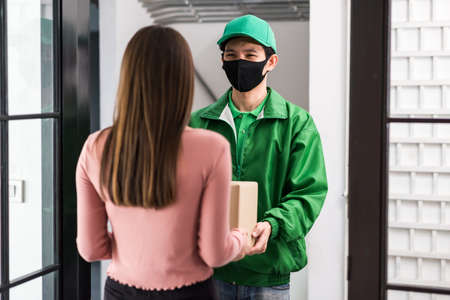 Rear of office woman receiving parcel from Asian courier deliveryman in uniform and face mask at door entrance. New normal to shopping by mobie phone application during covid19. 免版税图像