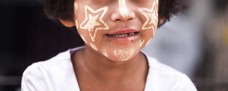 Closeup smiling face and dirty teeth of Mon Tribe girl with Thanaka, natural face powder base make-up made by ground bark with copy space for text, Sangkhlaburi, Kanchanaburi, Thailand. 免版税图像