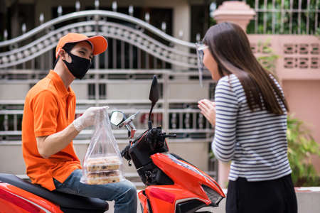 Mad food deliveryman with face mask in orange uniform wait on motorbike while woman customer sorry to pick up bakery late. COVID-19 pandemic. New normal to use smartphone app to order.