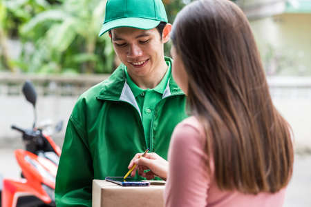 Woman putting signature in smartphone on cardboard box carry by deliveryman in green uniform with motorbike background. Parcel delivery for online order by mobile phone application.