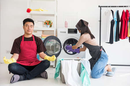 Asian young housewife woman with apron and purple hand protection glove load towel cloth to washing machine for cleaning laundry while husband perform lotus hand yoga. housework in weekend.