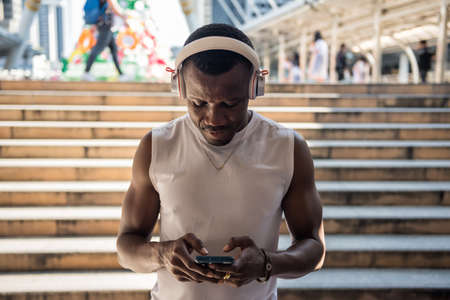 Black African-American man using smartphone to chat and listen stream online music by earphone in city. break after jogging or running exercise. Healthy with technology lifestyle. 免版税图像