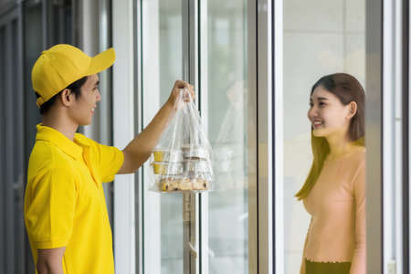 Happy businesswoman in meeting room seeing delivery bakery from Deliveryman in yellow uniform to pick up cake and bakery. girl wait for food. Lifestyle in working day. New normal to order food by app. 免版税图像