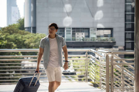 Chinese or Korean solo tourist man pulling suitcase to travel alone in city. Backpacker summer vacation in urban town. Single Asian traveller on holiday at foreign country.