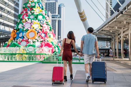 Rear of Asian tourist couple hold hands while walk and pull two travel suitcases at modern urban city with big Christmas tree during 2020 x'mas and 2021 new year. Happy vacation for husband and wife. 免版税图像