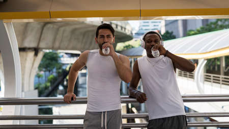 Young white and black African American friends rest and drink water on city skywalk after jogging or running workout. Athlete men relax after exercise in modern city. Sport healthy lifestyle in town.