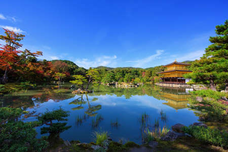 Golden Pavilion of Kinkakuji temple with autumn foliage colors around pond with skyline reflection, Kyoto, Japan. Famous travel landmark at Rokuonji in Kansai. 新闻类图片