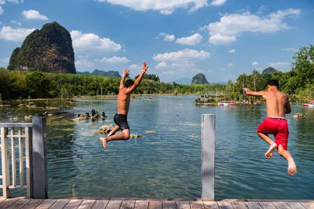 Rear of two happy young friends jump to lake with blue sky and Limestone mountain background at Klong Rood, Krabi, Thailand. Group of boys at famous travel destination to kayak and swim.