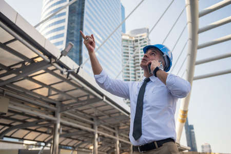 Old American engineer with hard hat point finger and call to support team at construction site in modern city. Architect project manager or senior engineering boss worry about project delay. 免版税图像