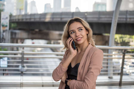 Attractive beautiful American businesswoman talking on smartphone to discuss business project in Bangkok city. Smile happy young woman with golden hair talking with good feeling.