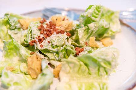 Cesar salad of romaine lettuce, cheese, bacon, and crispy garlic bread on plate. Healthy eating italian food lifesyle.