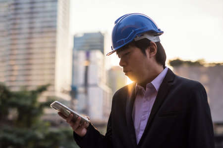 Asian Senior engineer manager, 40s middle age, with safety hard hat use app on smartphone to check project plan blueprint and timeline at construction site in city at sunset.