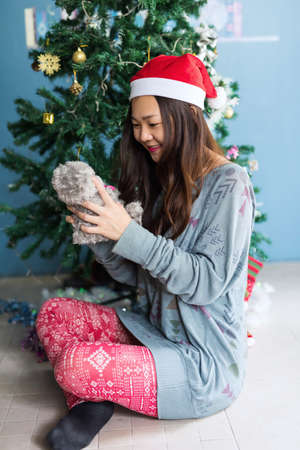 Asian Chinese girl teenager in a knitted sweater and santa claus hat with teddy bear at the Christmas tree. mas holiday and 2021 new year celebration in house concept. 免版税图像