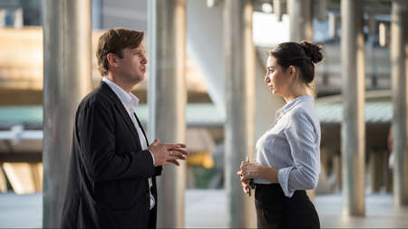 Angry pout American businesswoman wife look at her husband to explain and aplologize for mistake. Love conflict or problem for couple in urban city. woman and man arguing