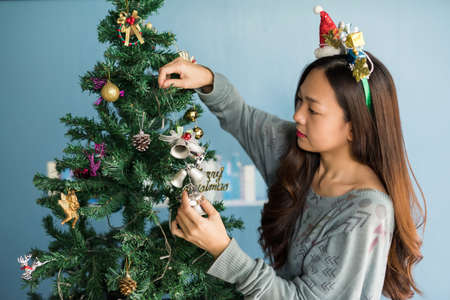 Beautiful attractive Chinese woman with Santa Claus hat and sweater decorate silver bell into Christmas tree near blue wall. Xmas holiday and 2021 new year celebration in house concept. 免版税图像