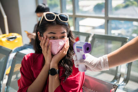 Shocked traveller with mask see her body temperature from Medical infrared thermometer on officer hand. woman in airport terminal get flight cancel due to potential of Corona or covid-19 virus.