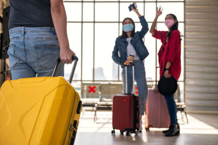 man pull luggage while his friends with face mask waving hand to say hi at airport departure terminal.Travel with new normal to prevent covid-19 pandemic disease.