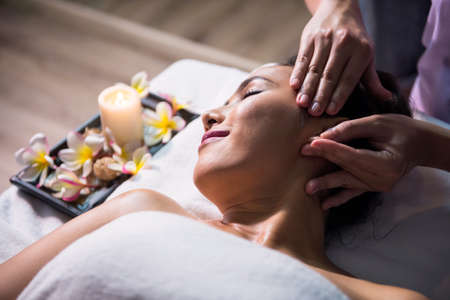Thai oil facial massage on bed to beautiful young asian Relaxing woman in spa salon. Health care and Relax to heal pain concept. Alternative healthcare industry.