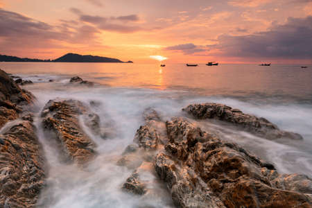 motion wave through rock at sunset with twilight sky. Beautiful Andaman seascape at Kalim Patong beach in Phuket, Thailand. famous travel destination for summer holiday vacation.