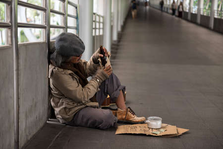 Asian 60s Homeless old man or beggar drink bottle of beer at city sky walk in winter. Poverty and social issue concept.
