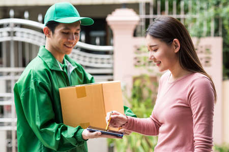 smiling young Asian woman signing receive digital signature on smartphone to accept a delivery boxes from courier deliveryman in green jacket and cap uniform. postal deliver service