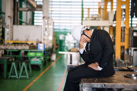 Stressed Factory manager or businessman owner with hardhat sit on machine with factory background. Depress feeling for bankruptcy, unemployed, or fired.