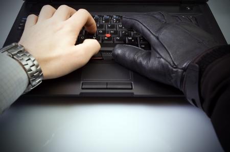 identity thieves: Concepto de seguridad con el empresario y hacker de manos en el teclado de la computadora port�til