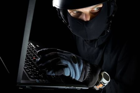 balaclava: Security concept with sneaky thief and laptop at night