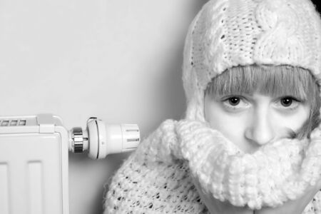 Winter at home, sad woman beside a cold heater photo